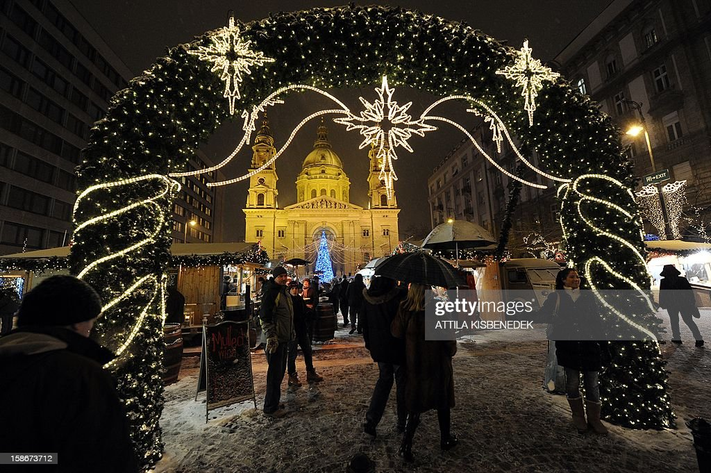 People walk to look for Christmas gifts in front of the St. Stephan Baslic of Budapest on December 23, 2012 at a Christmas market in the heart of the city.