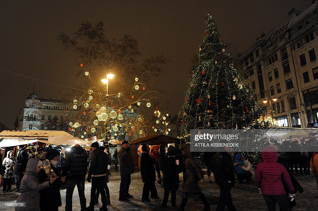 People walk to look for Christmas gifts in Vorosmarty square of Budapest on December 23, 2012 at a Christmas market in the heart of the city. AFP PHOTO / ATTILA KISBENEDEK