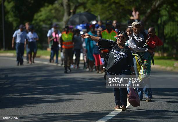 People walk to see the coffin of South African former president Nelson Mandela lying in state outside the Union Buildings on December 12 2013 in...