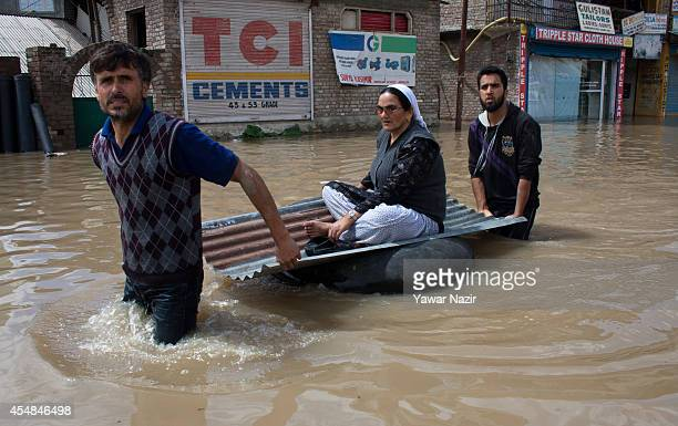 People walk to the safer places in a submerged road in a flooded residential area on September 07 2014 in Srinagar the summer capital of Indian...