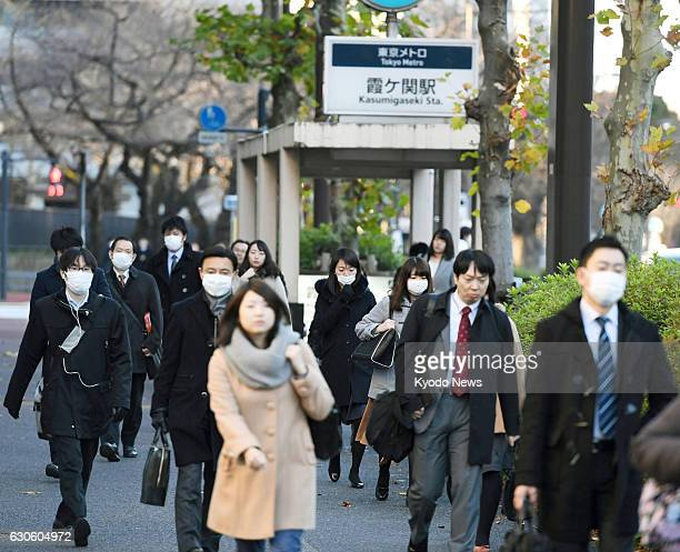 People walk to their workplaces in Tokyo's Kasumigaseki district on Dec 28 the last working day of the year for many people in Japan