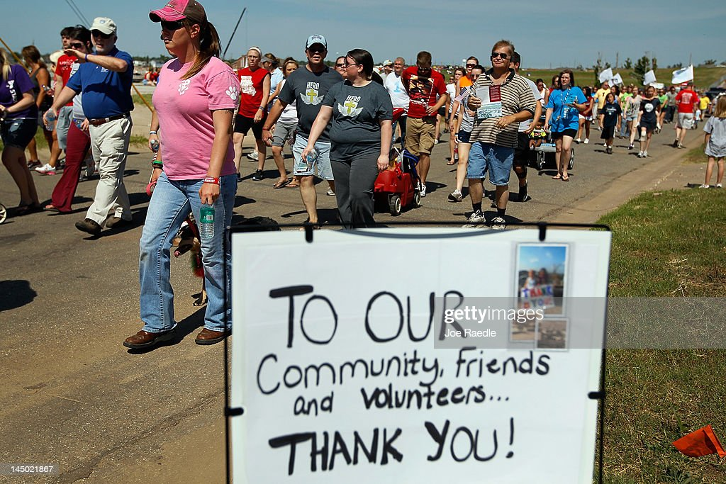 People walk together during a city sponsored Walk of Unity through the area that was ravaged by a massive tornado one year ago today on May 22, 2012 in Joplin, Missouri. The EF-5 tornado devastated the area leaving behind a path of destruction along with 161 deaths and hundreds of injuries, but one year later there are signs that the town is beginning to recover.