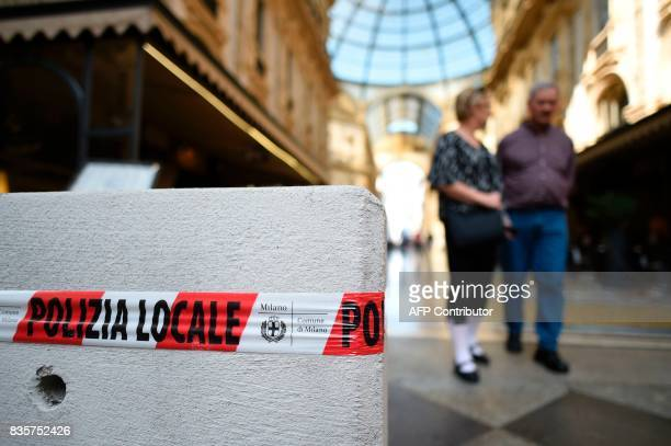People walk towards a concrete barrier placed at the entrance of the Vittorio Emanuel II gallery close to the Duomo in Milan northern Italy on August...