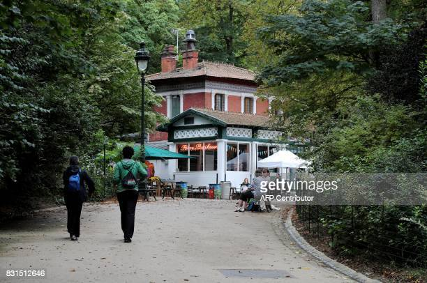 People walk towards the Rosa Bonheur bar ButtesChaumont Park in Paris on August 13 2017 The ButtesChaumont Park created in 1867 celebrates its 150th...