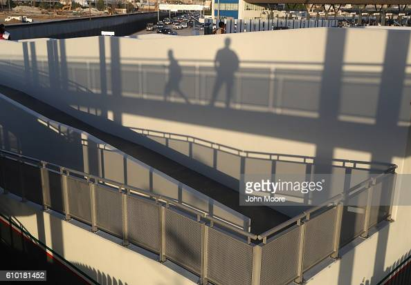 People walk towards the United States on the USMexico border crossing on September 23 2016 in Tijuana Mexico Securing the border and controlling...