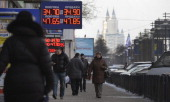 People walk under a chain of currency exchange offices in central Moscow on January 27 as the euro shot up by about one percent to 4763 rubles in...