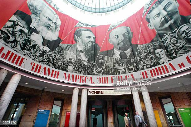 People walk under a giant poster featuring Communism's great exponents Karl Marx Friedrich Engels Lenin and Stalin adorning the entrance hall of a...