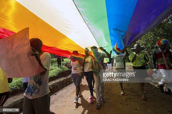 People walk under a giant rainbow flag as they take part in the Gay Pride parade in Entebbe on August 8 2015 Ugandan activists gathered for a gay...