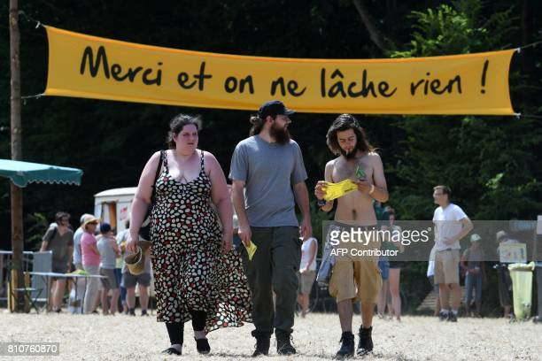 People walk under a sign reading 'Thank you we do not lick anything' during a twoday meeting organised by opponents to a controversial international...