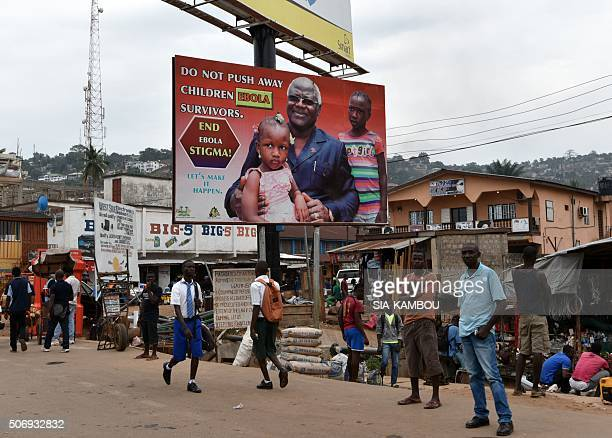 People walk under an Ebola's information board featuring Sierra Leone's president Ernest Bai Koroma on January 22 2016 in a street of Freetown / AFP...