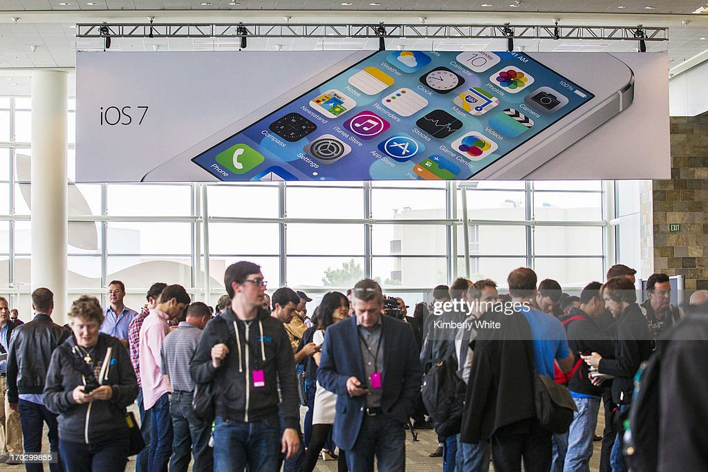 People walk under an iOS7 sign at the 2013 Apple WWDC at the Moscone Center on June 10 2013 in San Francisco California Apple introduced a new mobile...