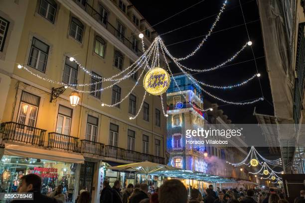 People walk under Christmas and New Year light displays in Rua Augusta on December 9 2017 in Lisbon Portugal The city shows a variety of light...