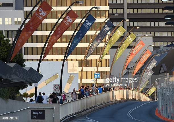 People walk under G20 banners adorning a bridge bordering the Southbank precinct where the G20 Summit will be held in Brisbane on November 14 2014...