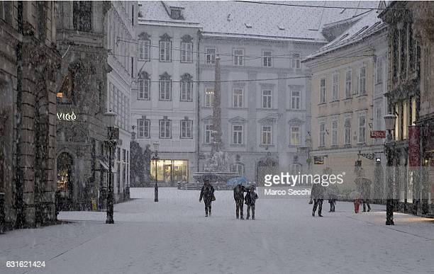 People walk under heavy snow on Mesni trg on January 13 2017 in Ljubljana Slovenia Most of Slovenia was covered by heavy snowfalls for the first time...
