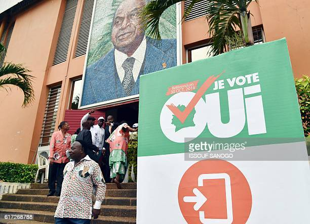 People walk under portrait of Ivory Coast's first president Felix HouphouetBoigny at the entrance of the stadium in his name in Abidjan on October 22...