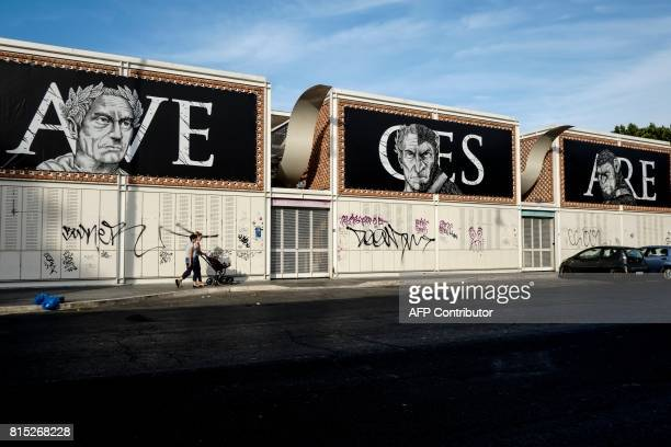 People walk under street art reading 'Ave Cesare' next to Testaccio market in central Rome on July 15 2017 / AFP PHOTO / Andreas SOLARO