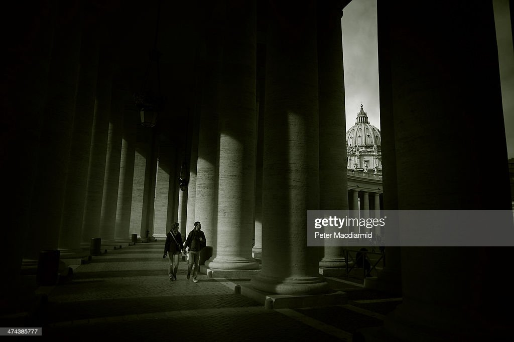 People walk under the colonnades in St Peter's Square before Pope Francis gives the Angelus blessing on February 23, 2014 in Vatican City, Vatican. Pope Francis created 19 new cardinals yesterday in a ceremony in St Peter's Basilica.