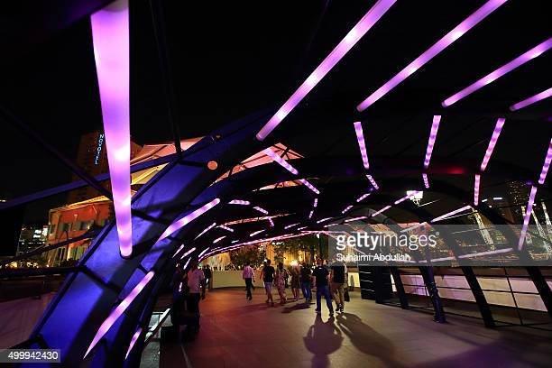People walk under The RIBbon @ Read Bridge light installation during the Christmas by the River launch on December 4 2015 in Singapore The...