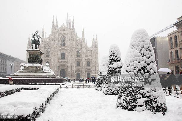 People walk under the snow near the Piazza Del Duomo on January 6 2009 in Milan Italy Parts of northern and central Italy are experiencing freezing...
