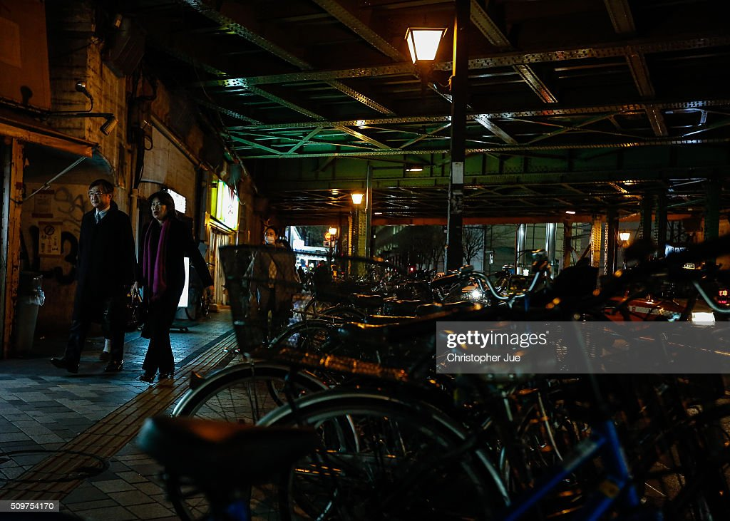 People walk under the train tracks in downtown Tokyo on February 12, 2016 in Tokyo, Japan. The Nikkei Stock Average finished 11% down for the week, its biggest weekly drop since October 2008, and the index for the day ended 4.8% down, the lowest since October 2014.