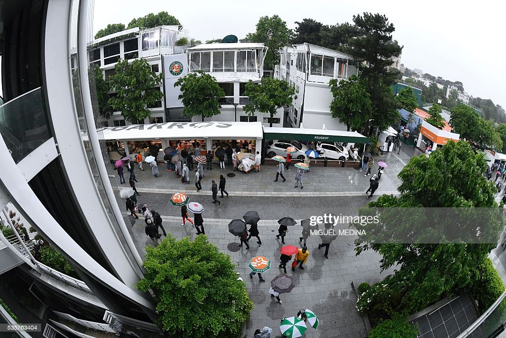 People walk under umbrellas as play is suspended due to rain at the Roland Garros 2016 French Tennis Open in Paris on May 30, 2016. / AFP / MIGUEL