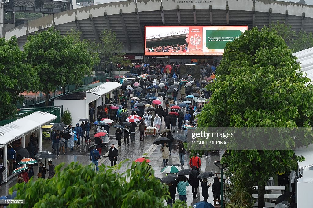 People walk under umbrellas outside the Suzanne Lenglen court as play is suspended due to rain at the Roland Garros 2016 French Tennis Open in Paris on May 30, 2016. / AFP / MIGUEL