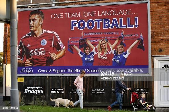People walk underneath an Aldershot football team billboard near The Electrical Services Stadium in Aldershot on September 9 2014 Aldershot Town may...