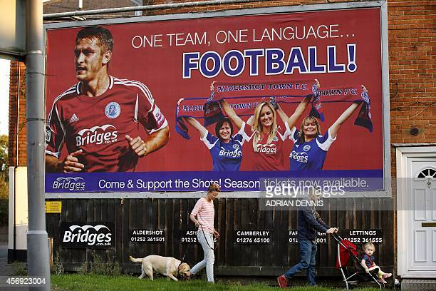 People walk underneath an Aldershot football team billboard near The Electrical Services Stadium in Aldershot on September 9 2014 Aldershot Town may...