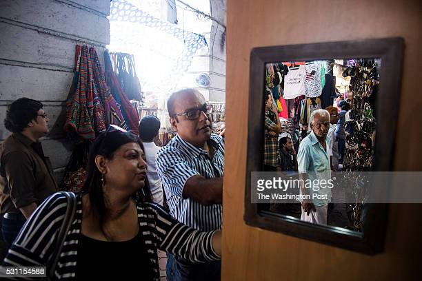 People walk up and down Shahid Bhagat Singh Road also known as the Colaba Causeway where many local and foreign goods can be found for sale in this...