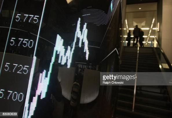 People walk up stairs next to a board showing the German DAX index during a trading session at Frankfurt stock exchange on September 30 2008 in...