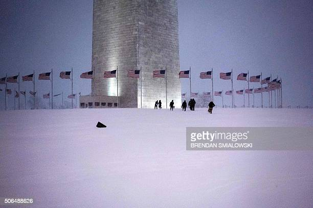 People walk up to the Washington Monument after a snowstorm January 23 2016 in Washington DC A deadly blizzard blanketed the eastern United States in...