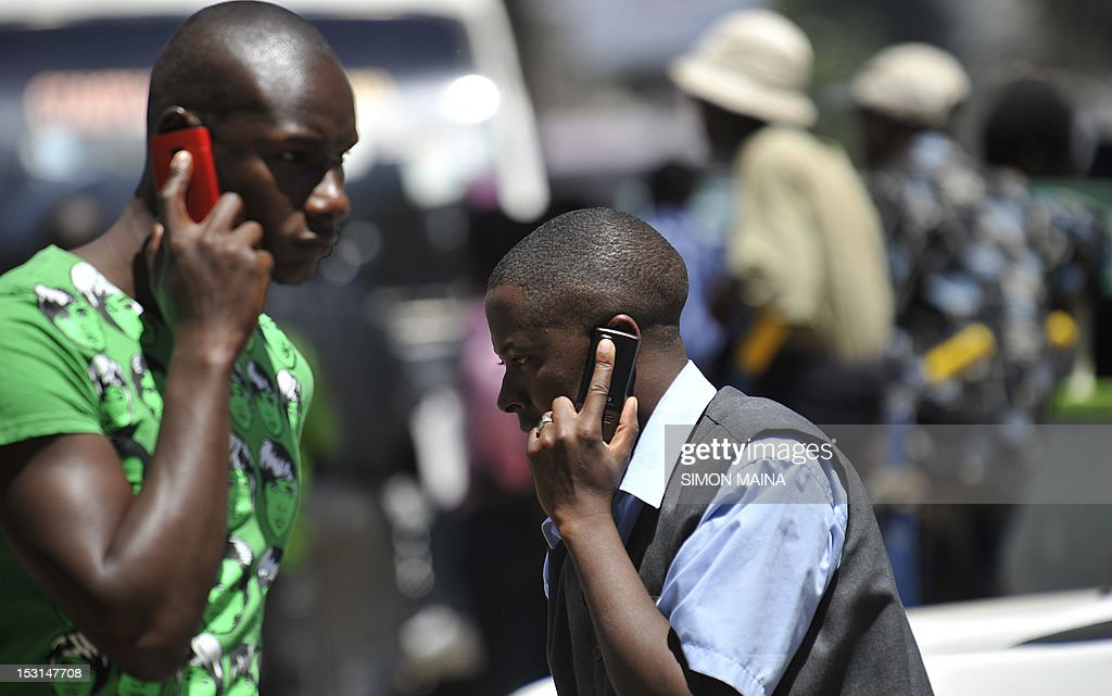People walk while speaking on the phone on October 1,2012 in Nairobi, as Kenya confirmed a switch-off of counterfeit mobiles will take place at the end of the month.The mobile networks will be forbidden from activating new 'fake' devices bought after October 1. Government officials said the move was designed to protect consumers from hazardous materials and to safeguard mobile payment systems and prevention of crime. The government said three million users were using counterfeit handsets as of June.