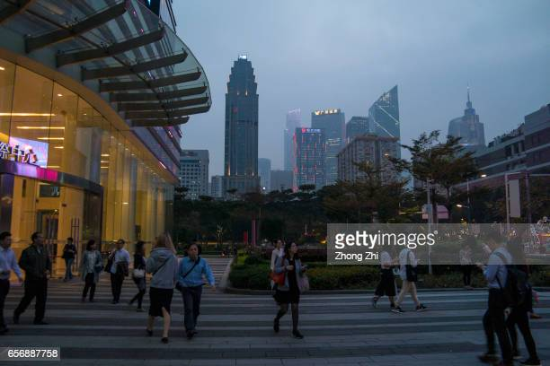 People walk while the high commercial and residential buildings rise in the distance in the Zhujiang New Town district on March 23 2017 in Guangzhou...