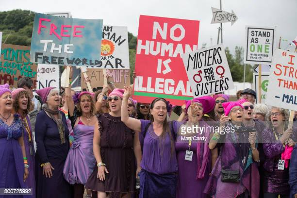People walk with banner at a profeminist event organised by the White Ribbon Alliance at The Park Stage at the Glastonbury Festival site at Worthy...