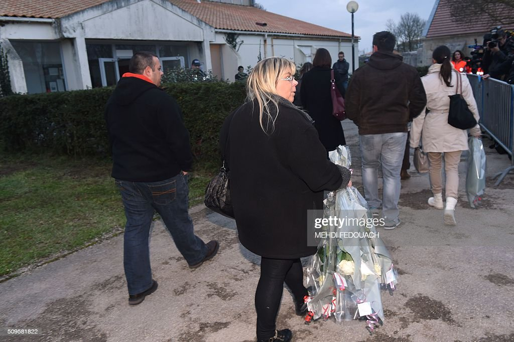 People walk with candles and flowers in Surgeres, on February 11, 2016, to pay tribute to the victims of the road accident between a school bus and a truck, killing at least six children. The head-on smash with a lorry carrying rubble came around 7:15 am (0615 GMT) in Rochefort in the western Charente-Maritime region. The school bus was carrying about 17 people, and three children suffered minor injuries in the accident, a police source said. / AFP / MEHDI FEDOUACH