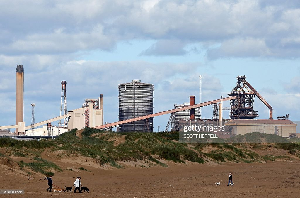 People walk with dogs along a beach near the former Corus steelworks in Redcar, north-east England on June 27, 2016. Top Brexit campaigner Boris Johnson sought Monday to build bridges with Europe and with defeated Britons who voted to remain in the EU in last week's historic referendum. Britons voted by 52 percent to 48 percent in favour of leaving the European Union in a June 23 vote that exposed deep divisions in the country and sent shockwaves through the world. / AFP / SCOTT