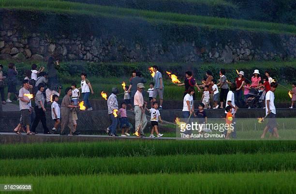 People walk with fire torches during 'Mushi Okuri' ritual at Shodoshima Island on July 2 2003 in Tonosho Kagawa Japan The ritual 'Mushi Okuri ' held...
