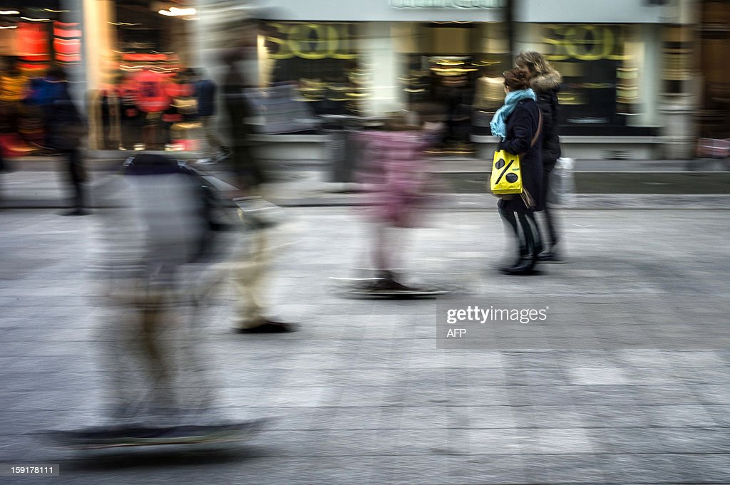 People walk with shopping bags on the opening day of the winter sales on January 9, 2013 in Lyon, in central France.