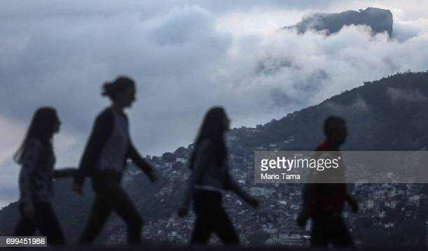People walk with the Vidigal 'favela' community in the distance on the first day of winter on June 21 2017 in Rio de Janeiro Brazil Today's solstice...