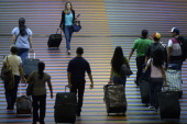 People walk with their luggage at the Maiquetia international airport that serves Caracas on July 3 2014 A survey by pollster Datanalisis revealed...