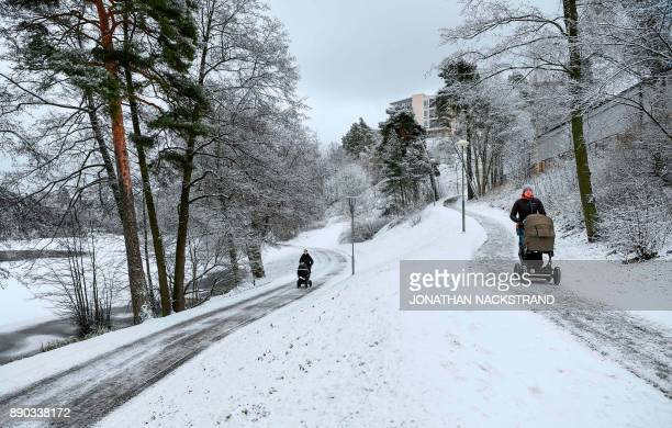 People walk with their strollers next to Lotsjon lake after snow fall on December 11 2017 in Sundbyberg near Stockholm High winds and heavy snow in...