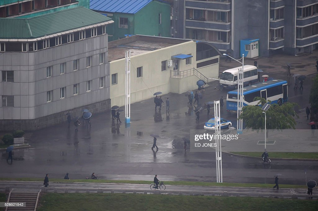 People walk with umbrellas during their morning commute in Pyongyang on May 6, 2016. North Korea will on May 6 launch its highest-level ruling party meeting in almost 40 years, with delegates set to heap praise on its nuclear arsenal as a 'precious sword' amid fears of a fresh atomic test. / AFP / Ed Jones