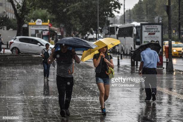 People walk with umbrellas on August 22 2017 during a heavy rain at the Aksaray district in Istanbul / AFP PHOTO / OZAN KOSE