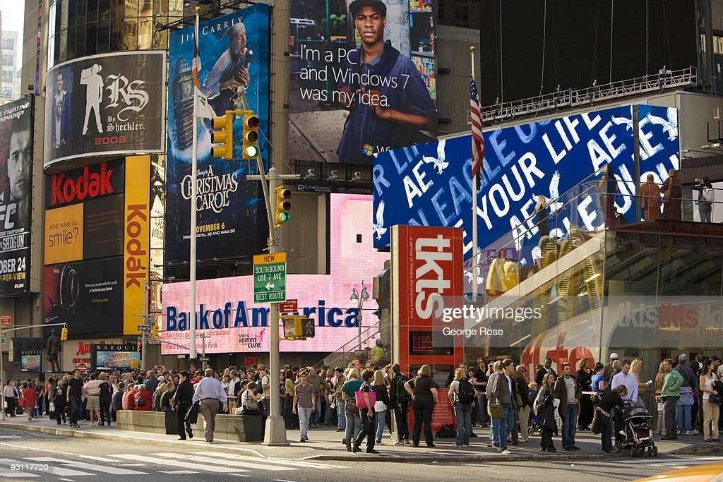 People walking along 7th Avenue near Broadway and Times Square are seen against a backdrop of advertising billboards in this 2009 New York, NY, early afternoon cityscape photo.