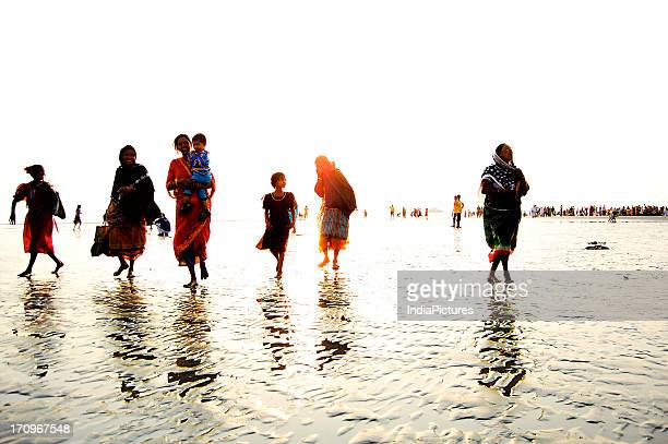 People walking along the beach with the waves beneath their feet West Bengal India