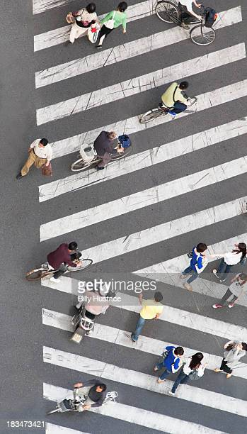 People walking and biking on a striped crosswalk