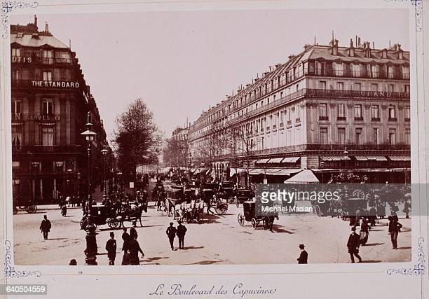 People walking and driving horse drawn carriages down the Boulevard des Capucines in Paris circa 18801889