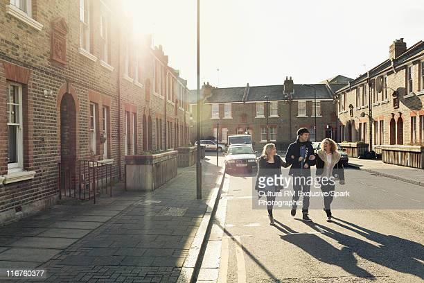 People walking arm-in-arm on city street