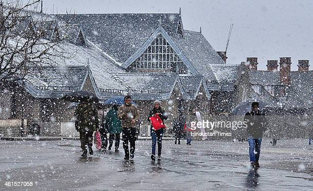 People walking at the ridge during snowfall on January 14 2015 in Shimla India Shimla and its surrounding resorts of Kufri Fagu and Narkanda had...