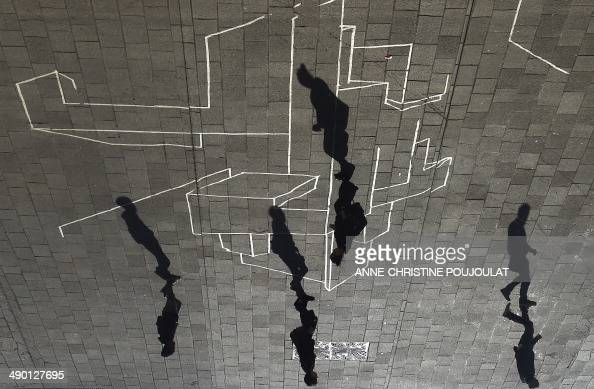 People walking by a street art work are reflected by the installation of British architect Norman Foster's entitled 'Ombrière' a work exhibited as...
